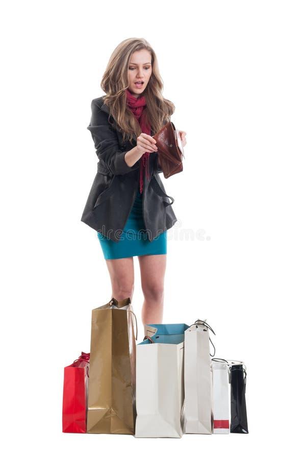 Besorgte Einkaufsfrau, welche die leere Geldbörse überprüft stockfotografie