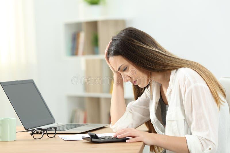 Besorgte Hausfrau, die Buchhaltung tut stockfoto