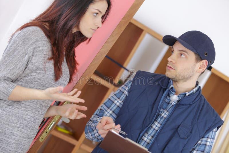 Besorgte Hausfrausitzungsservice-Arbeitskraft an der Tür zu Hause lizenzfreie stockbilder