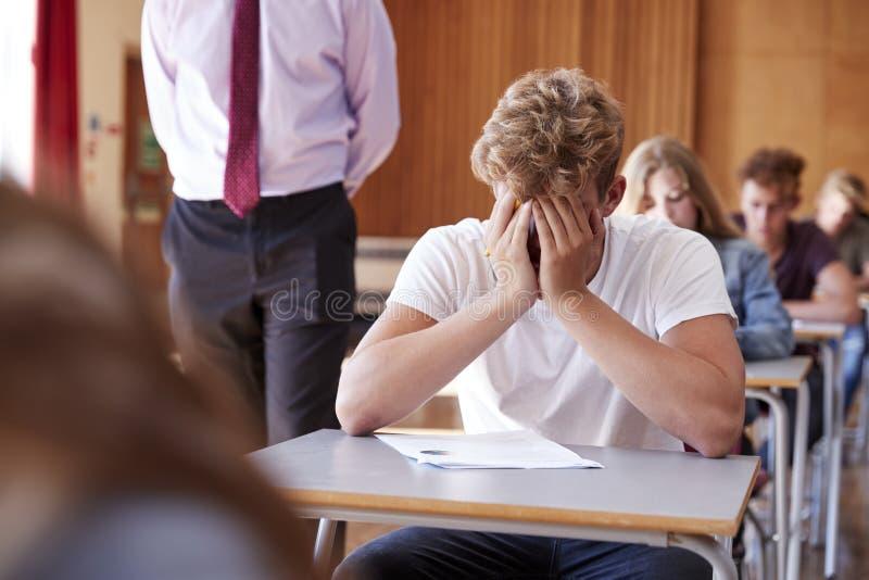 Besorgte Jugendstudenten-Sitting Examination In-Schule Hall lizenzfreie stockfotos