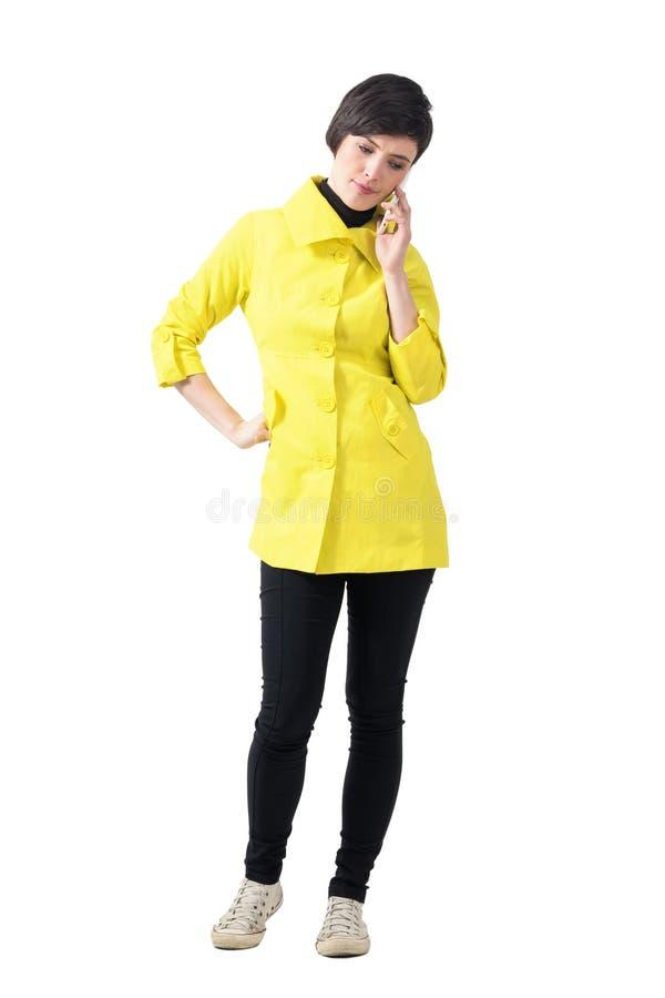 Besorgte junge Frau im gelben Mantel sprechend am Telefon, das unten schaut lizenzfreie stockbilder
