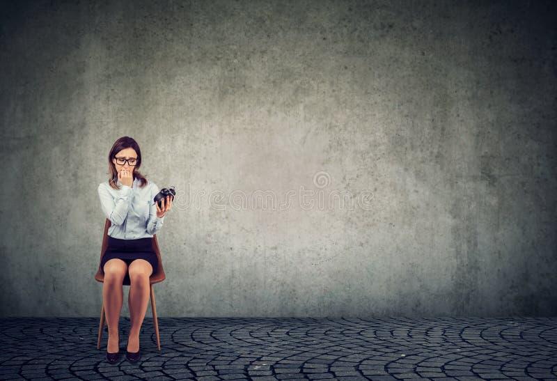 Besorgte junge Frau mit dem Wecker, der auf ein Interview wartet lizenzfreies stockfoto