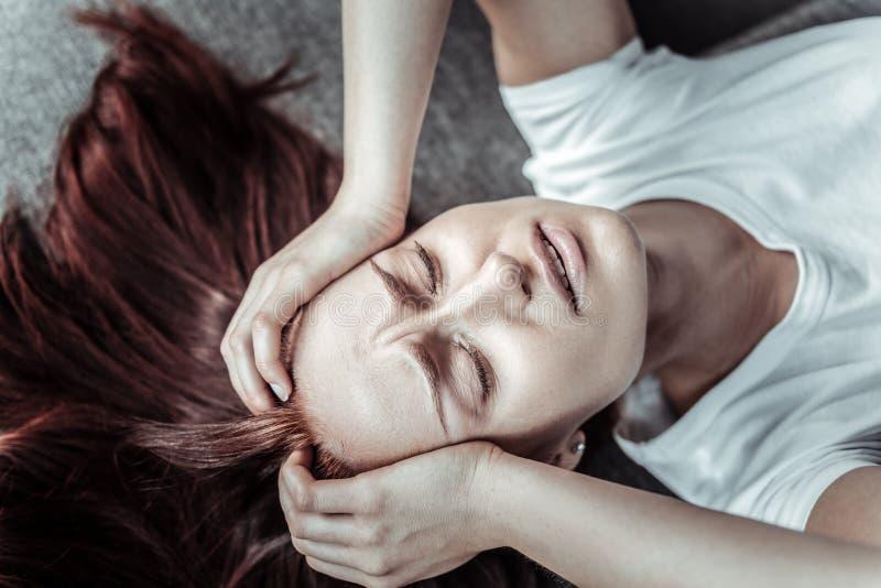 Besorgte leidende Schmerz der weiblichen Person stockfoto