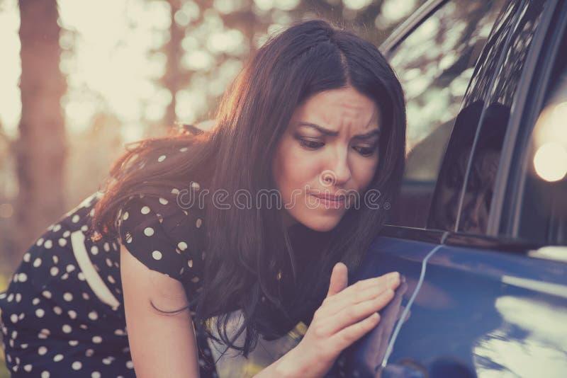 Besorgte lustige schauende Frau, die über Sauberkeit ihres Autos besessen ist stockbild