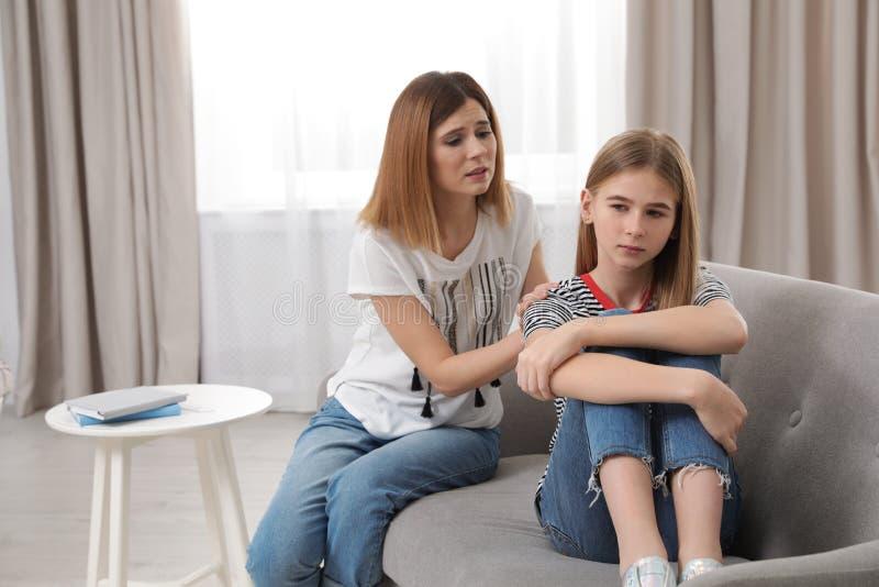 Besorgte Mutter, die mit ihrer Jugendlichtochter spricht stockbild