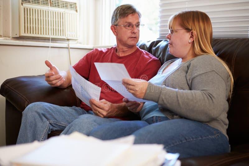 Besorgte Paare, die auf Sofa Looking At Bills sitzen lizenzfreies stockbild