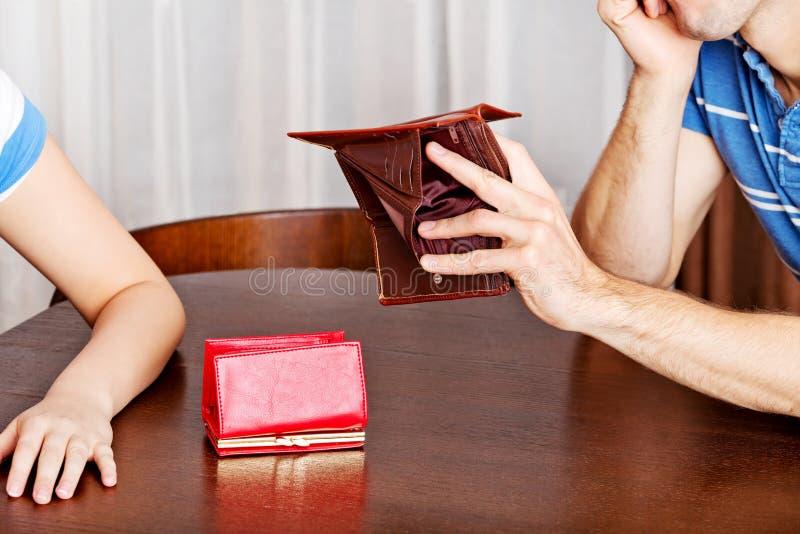 Besorgte Paare, die am Tisch mit leeren Geldbörsen sitzen stockbild