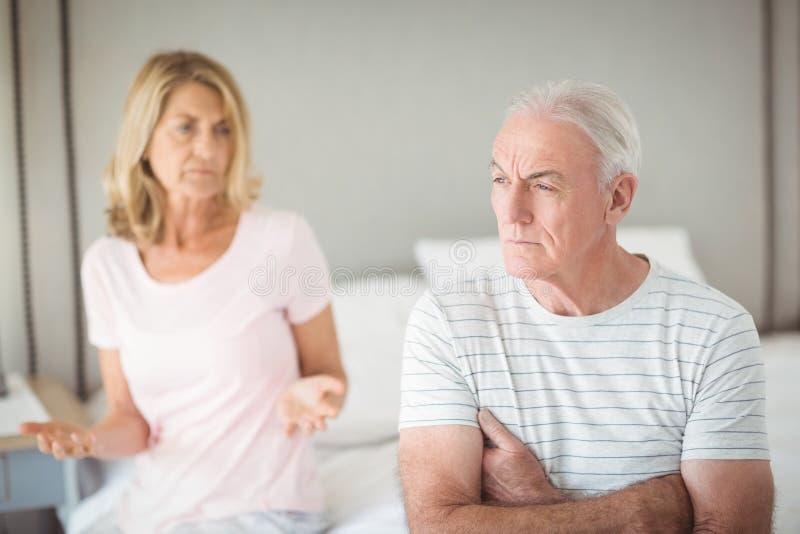 Besorgter älterer Mann, der auf Bett sitzt stockfotografie