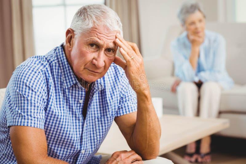 Besorgter älterer Mann, der auf Sofa sitzt lizenzfreie stockbilder