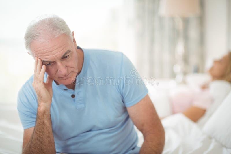 Besorgter älterer Mann, der im Schlafzimmer sitzt lizenzfreie stockfotografie