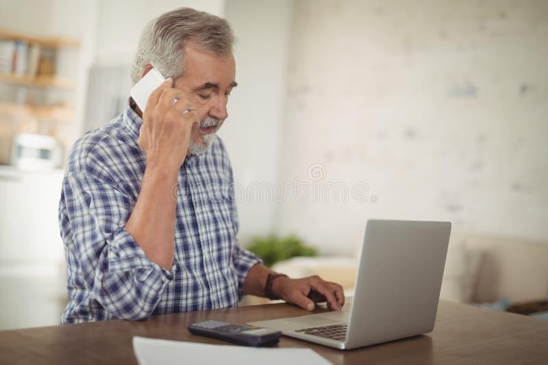 Besorgter älterer Mann, der am Telefon bei der Anwendung des Laptops nimmt stockbild
