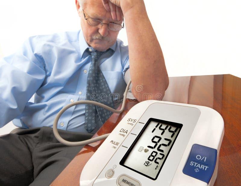 Besorgter älterer Mann mit hohem Blutdruck. stockfotografie