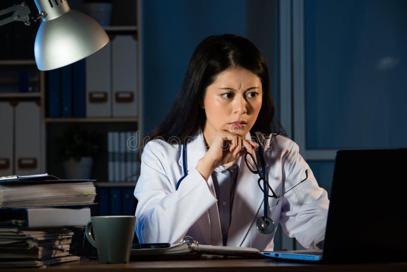 Besorgter Doktor, der schlechte Diagnose nachts hat stockfotos