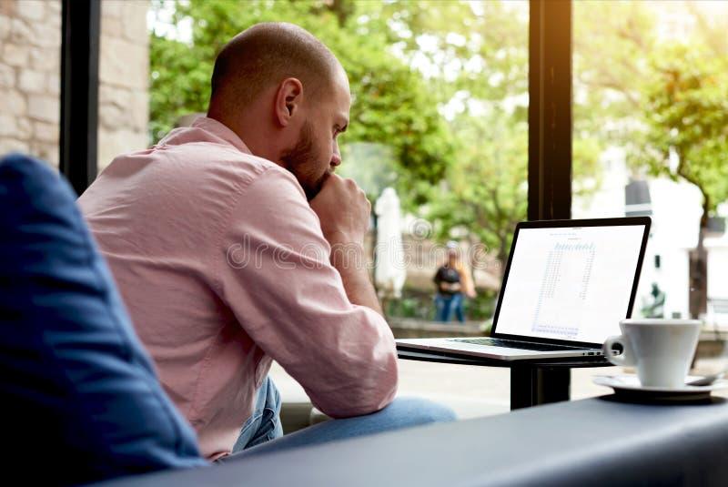 Besorgter Freiberufler, der an Notizbuch im modernen Café arbeitet lizenzfreie stockfotos