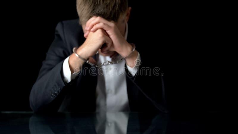 Besorgter Geschäftsmann in den Handschellen, die auf Arbeitsplatz, illegaler Handel, Mafia sitzen lizenzfreies stockbild