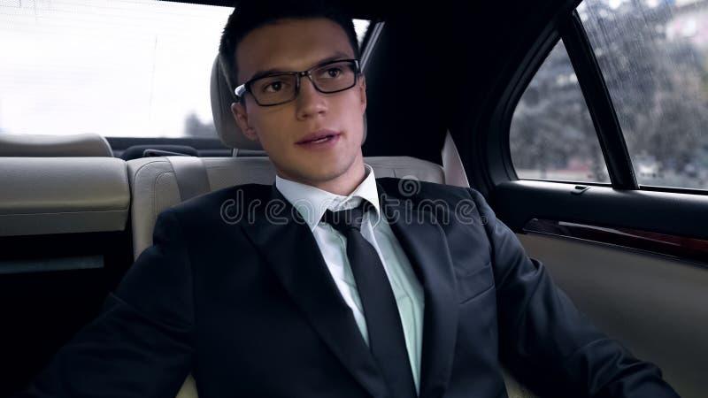 Besorgter Geschäftsmann, der auf dem Rücksitze des Luxusautos, spät für Arbeit, Hauptverkehrszeit sitzt lizenzfreie stockfotografie
