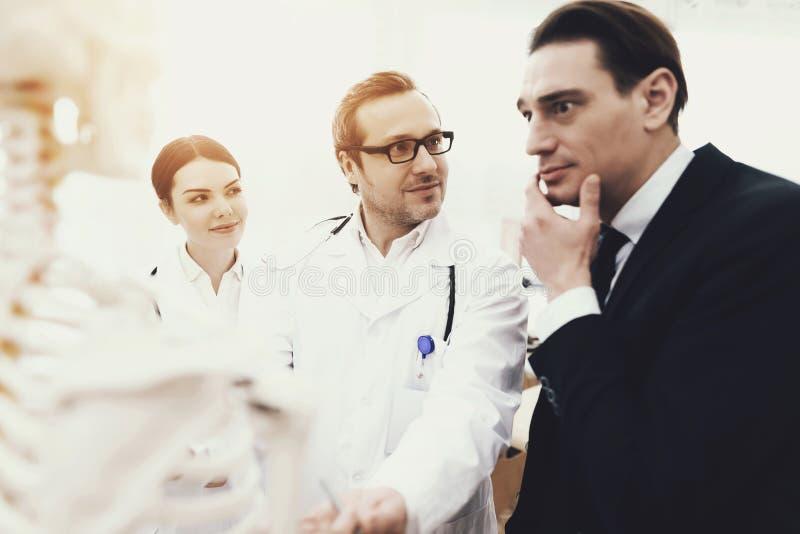 Besorgter Geschäftsmann an der Aufnahme mit Physiotherapeuten im Ärztlichen Dienst lizenzfreie stockfotos