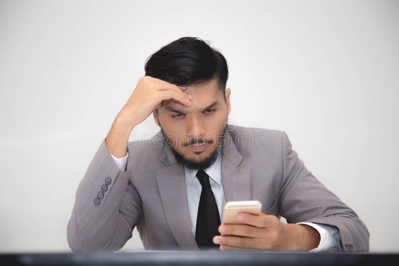 Besorgter Geschäftsmann, der mit Smartphone arbeitet lizenzfreie stockbilder