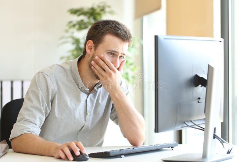 Besorgter Geschäftsmann, der online arbeitet lizenzfreie stockfotos