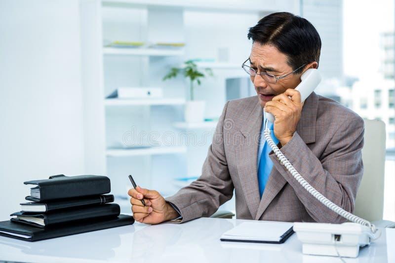 Besorgter Geschäftsmann im Telefon stockbild