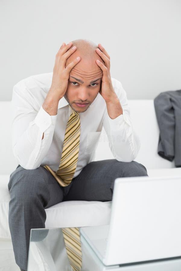 Besorgter Geschäftsmann mit dem Laptop Haupt zu Hause halten in den Händen lizenzfreies stockfoto