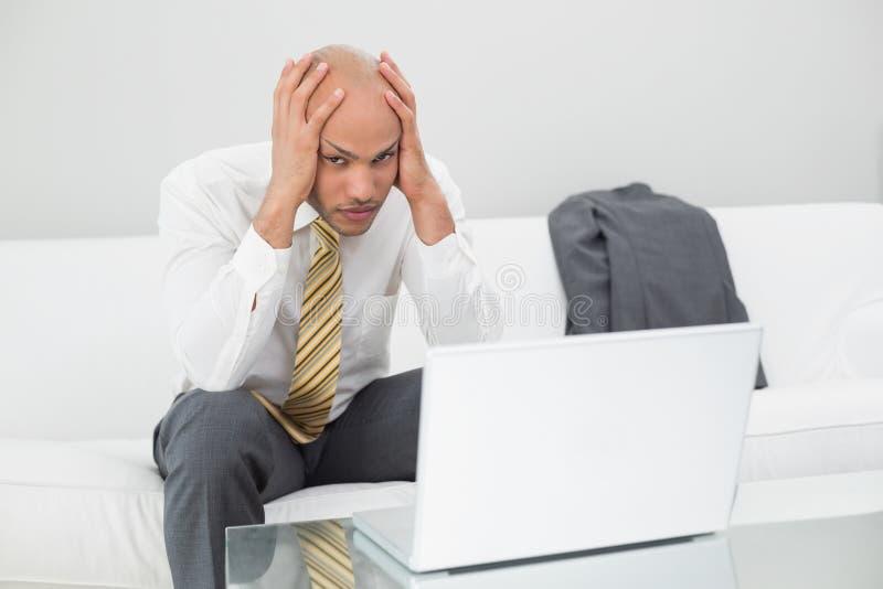 Besorgter Geschäftsmann mit dem Laptop Haupt zu Hause halten in den Händen stockbild
