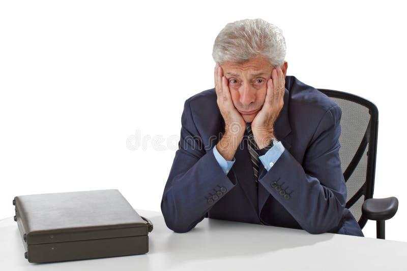 Besorgter Geschäftsmann steht Kinn auf Händen still lizenzfreie stockbilder