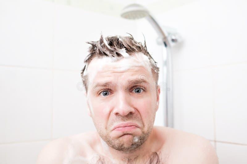 Besorgter geschäumter junger Mann, nachdem das Wasser unter der Dusche abgestellt wurde, die Kamera betrachtend stockbild