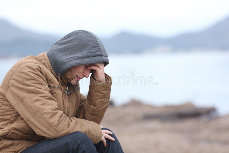 Besorgter Jugendlichkerl auf dem Strand im Winter stockbild