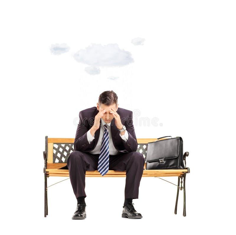 Besorgter junger Geschäftsmann, der oben auf Bank mit Wolke sitzt stockfotografie