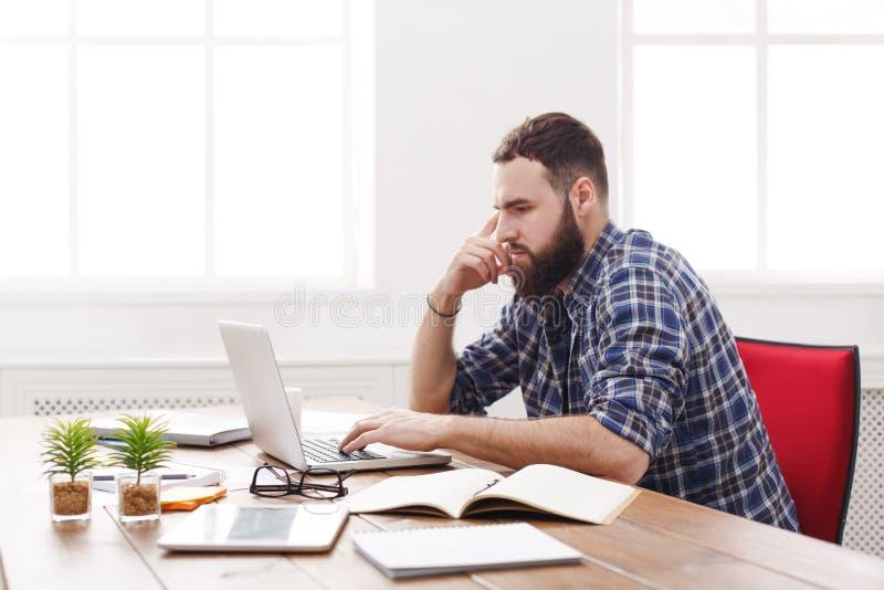 Besorgter junger Geschäftsmann, der am Schreibtisch auf dem Laptop schaut ernst arbeitet lizenzfreies stockfoto