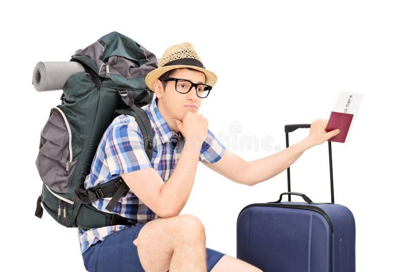 Besorgter männlicher touristischer haltener Pass und Aufwartung stockbilder