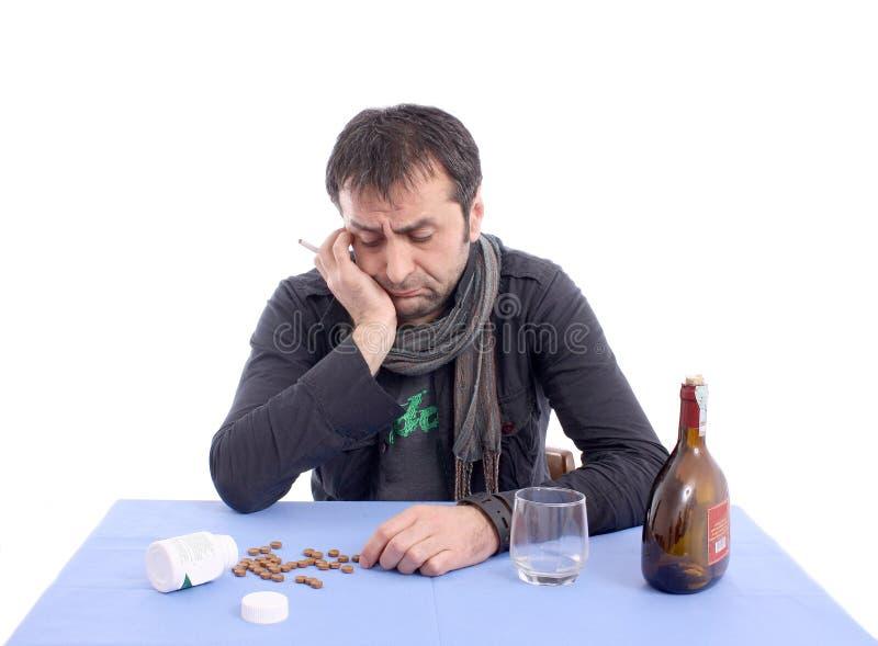 Besorgter Mann, der am Tisch sitzt lizenzfreie stockfotografie