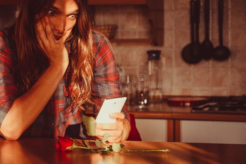 Besorgter Mann mit Rosafarbenem und Handy lizenzfreies stockbild