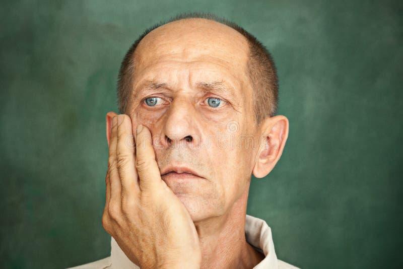 Besorgter reifer Mann, der seinen Kopf berührt lizenzfreie stockbilder
