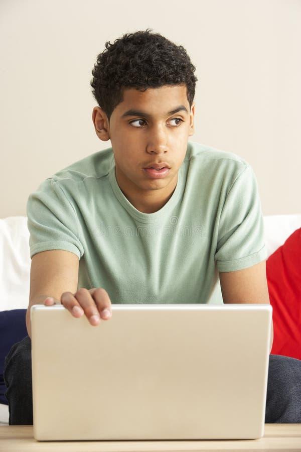 Besorgter schauender Junge, der Laptop verwendet stockbild