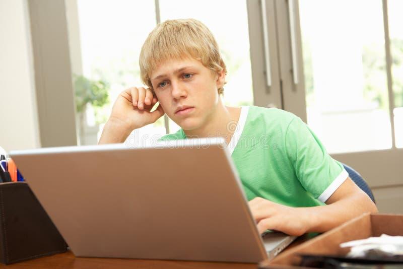 Besorgter schauender Teenager, der zu Hause Laptop verwendet lizenzfreie stockbilder