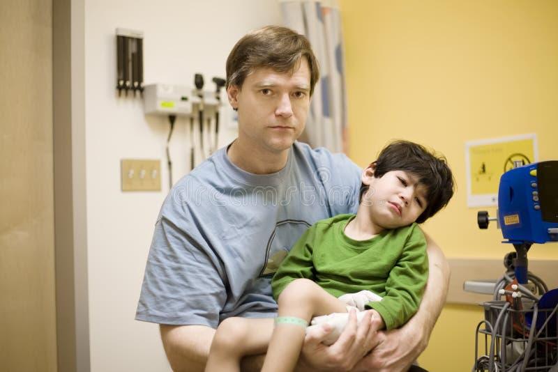 Besorgter Vater, der seinen kranken Sohn am Krankenhaus anhält stockfoto