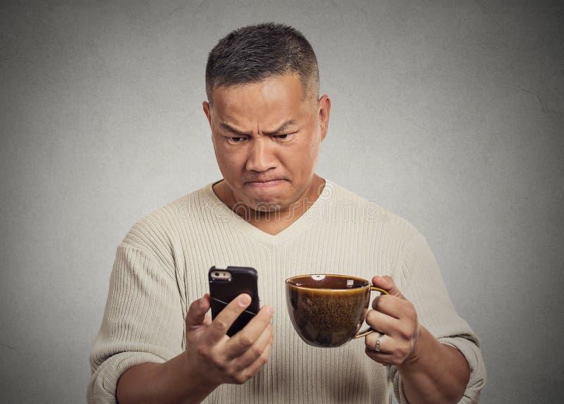 Besorgter verärgerter frustrierter Mann, der schlechte Nachrichten sms auf Smartphone liest lizenzfreie stockfotos