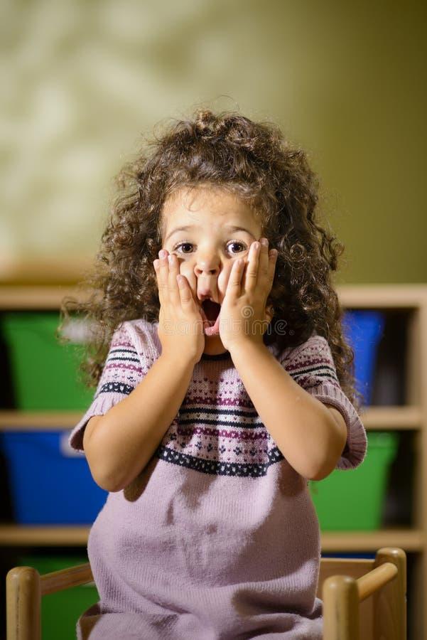 Besorgtes Kind mit dem Mund geöffnet im Kindergarten lizenzfreie stockbilder