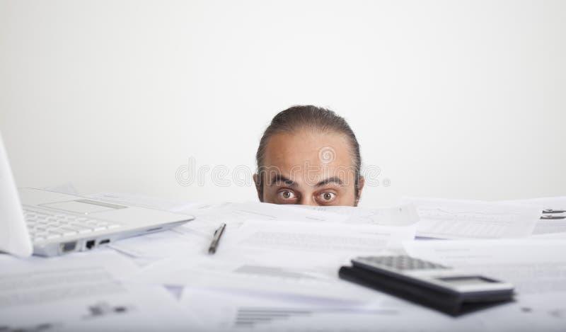 Besorgtes Manngesicht, das hinter Tabelle des Büros schaut lizenzfreie stockfotografie