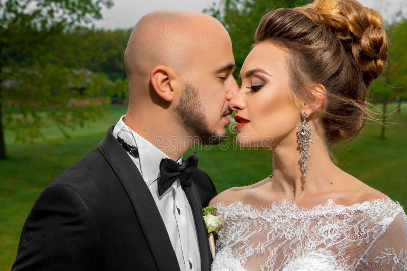 Besos casados hermosos jovenes de la pareja al aire libre fotos de archivo