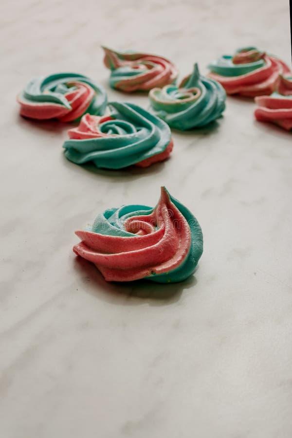 Besos de merengue apilados del arco iris, colores azules y rosados suaves en el fondo de mármol foto de archivo