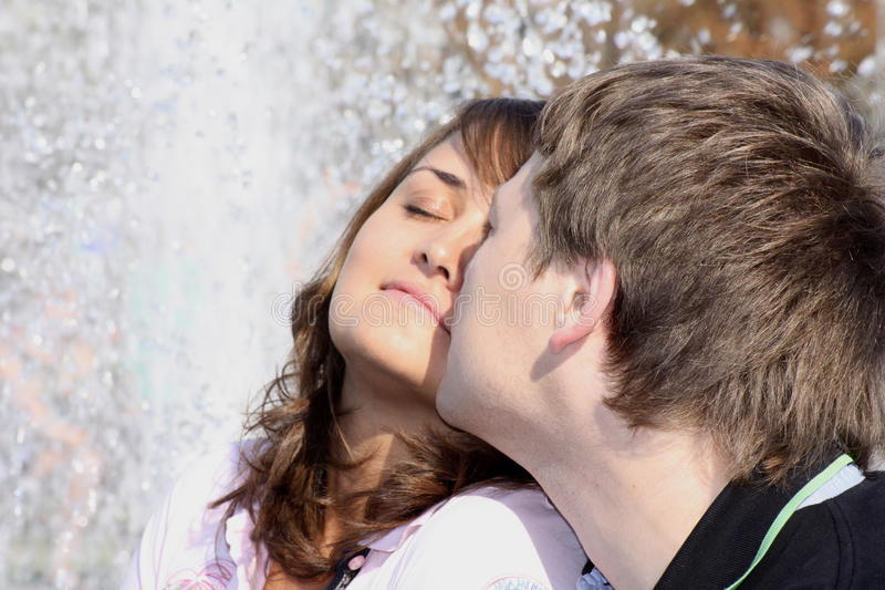 Besos (enamorados) de los pares que quieren contra una fuente fotografía de archivo