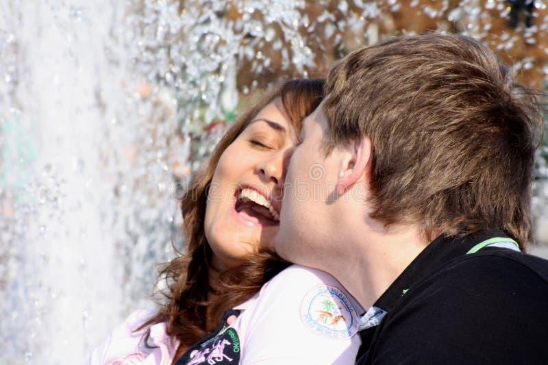 Besos (enamorados) de los pares que quieren contra una fuente imagenes de archivo