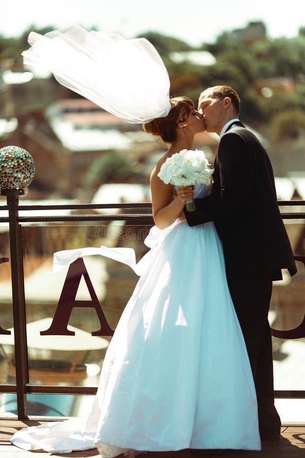 Besos felices de los pares de la boda en el tejado en un tiempo ventoso imagen de archivo libre de regalías