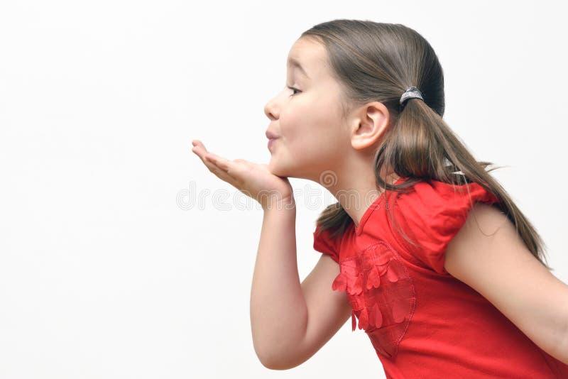 Besos que soplan de la niña foto de archivo