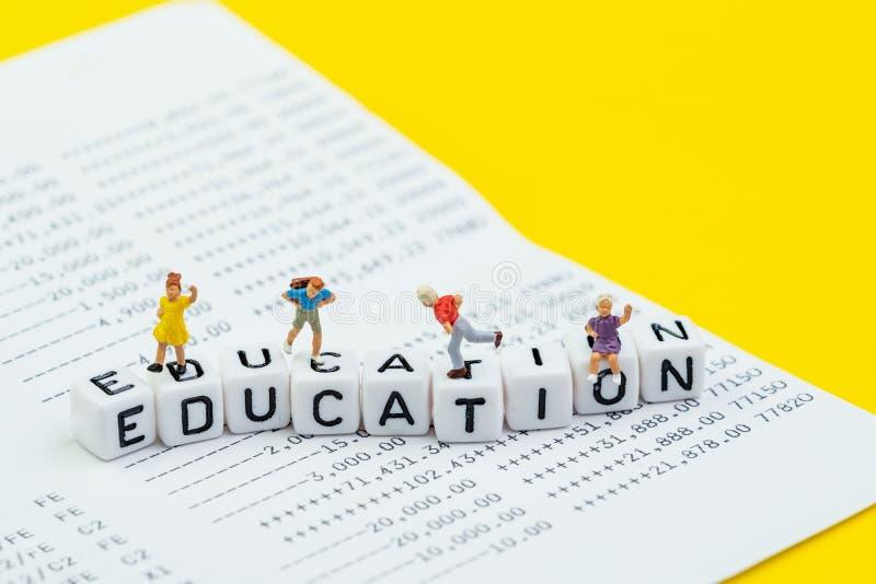 Besparing voor onderwijs of universiteit en schoolkostenconcept, miniatuurschoolkinderen die en op kubusblok lopen spelen met alf royalty-vrije stock fotografie