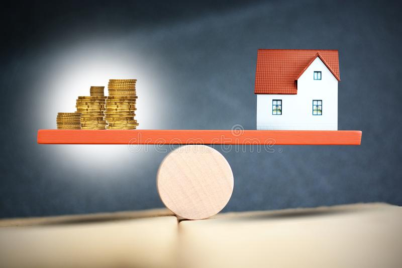 Besparingar eller fastighetsinvesteringbegrepp med hus- och kassapengar på skala royaltyfri bild