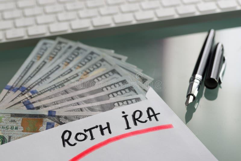 Besparingar för avgångbegrepp med Roth Ira som är skriftlig på det vita kuvertet med kassaUS dollar royaltyfria bilder